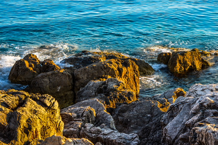 evening light on large rocks with cracks on the sea Stock Photo