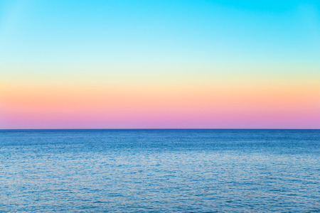 pastel sky with a calm sea beneath and a clear horizon