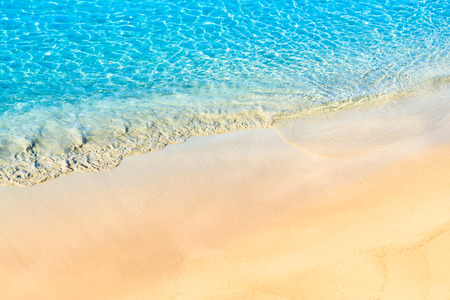 sandy beach and turquoise crystal clear water with small waves Stock Photo