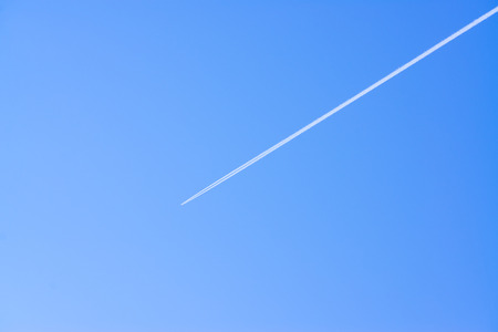 aircraft on a clear sky with a straight line of exhaust behind it photo