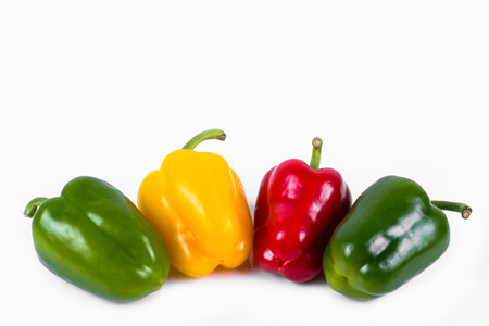 green red and yellow peppers in a row on a white background Stock Photo