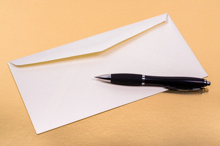 copys pace: unsealed white envelope with a ballpoint pen on the side on a gold background Stock Photo