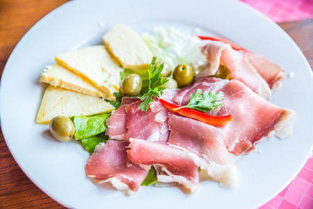 cheese ham and olives on a white plate Stock Photo