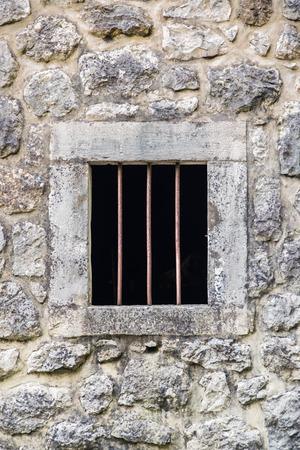 iron barred: barred prison window with stone walls around Stock Photo