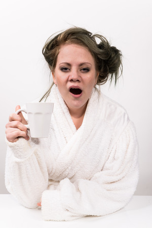 a white robe: tired woman holding coffee cup in her hand and wearing a white robe wearing Stock Photo