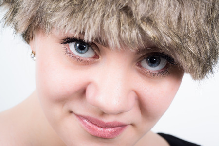 Closeup of charming young woman looking straight into the camera with a fur hat in front of a white background Stock Photo