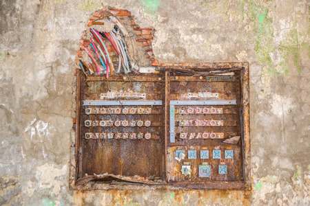 old rusty fuse box with broken dangerous wires above Stock Photo