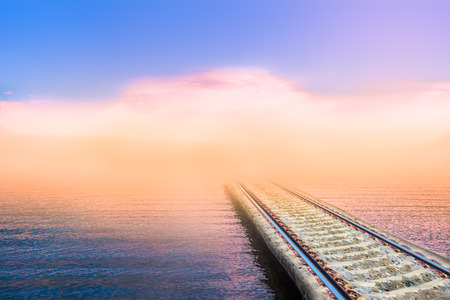 nowhere: tranquil scene of a railroad to nowhere in the sea with fog Stock Photo