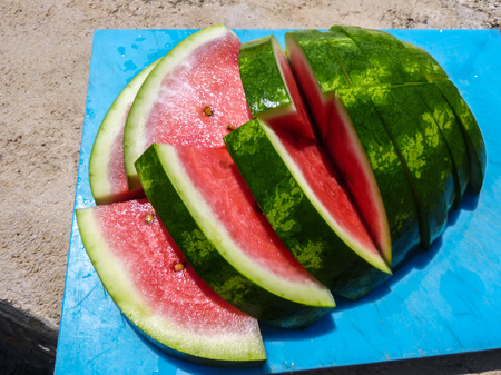 sliced watermelon on a cutting board in the sun Stock Photo