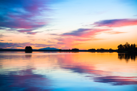 colorful sunset over a calm lake with mountains in the background