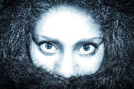 personne en colere: femme congelé dans un manteau de fourrure regardant droit dans la caméra avec des yeux bleus