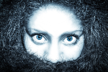 angry people: frozen woman in a fur coat looking straight into the camera with blue eyes