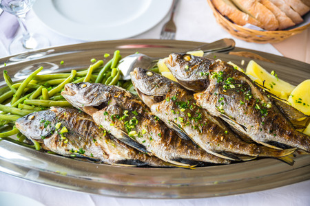Four grilled fish on a plate with potatoes and vegetables in the Mediterranean region