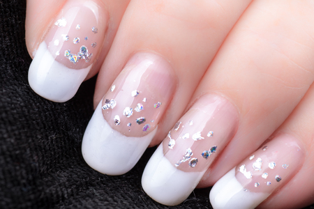 nails with a French manicure and silver tinsel on a black background