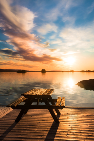 sweden resting: bench on a wooden pier at sunset in northern Sweden