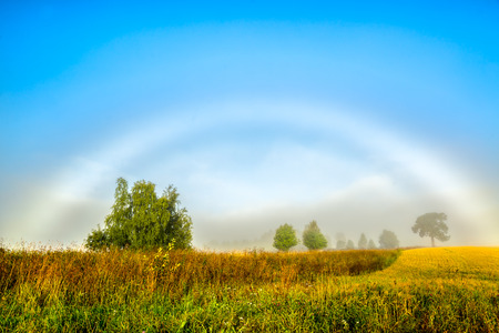 horizontals: beautiful morning with a misty rainbow in front of a blue sky