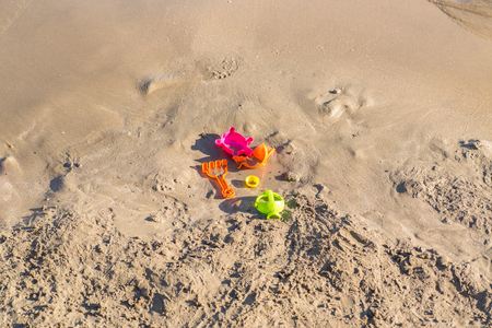forgotten toys in different colors on a sand beach