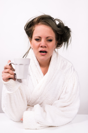 very tired young woman holding a coffee cup and wearing a bathrobe