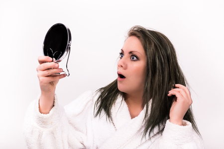 brown haired woman looking shocked at herself in a mirror while wearing a bathrobe
