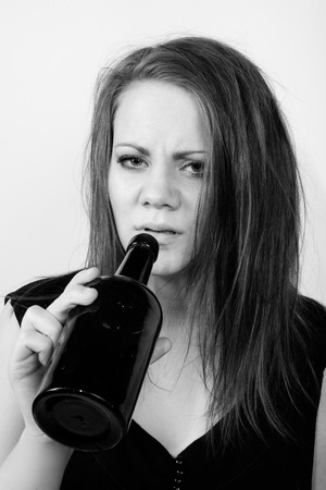 depressed young woman drinking from a wine bottle and looking straight into the camera
