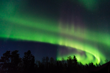 green and pink aurora borealis on a starry sky in the north of Sweden Stock Photo