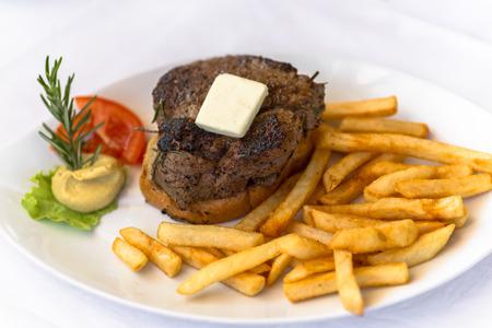 carnes y verduras: plato blanco con carnes a la brasa y patatas fritas y verduras