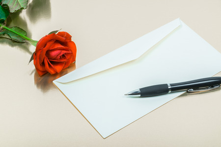 red rose with a pen and a blank letters on a gold background