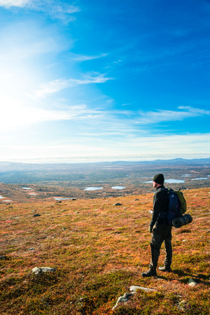 sweden resting: young man at the top  looking out over the view in northern Scandinavia Stock Photo