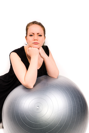 reluctant: determined woman leaning over a pilates ball with a white background Stock Photo