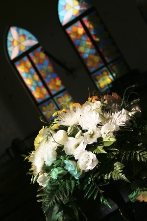Flowers in front of colorful stained glass windows Editorial