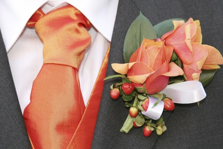 Grooms orange tie and roses