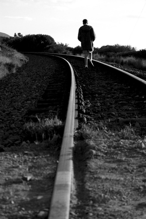 Boy walking on railway track