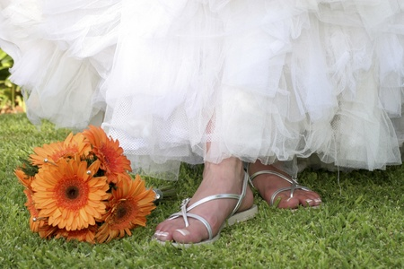 ornage gerbera bouquet next to brides feet  Stock Photo