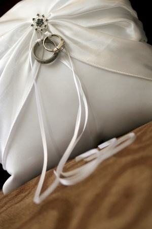 White cushion with wedding rings fastend with white ribbon