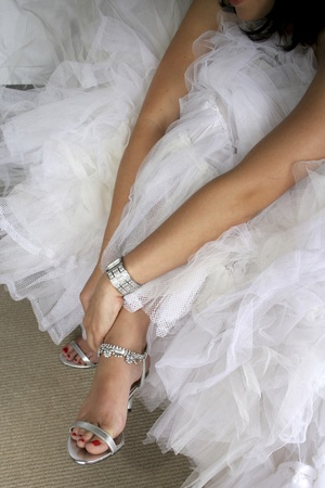 Bride in white wedding dress putting on silver shoes Stock Photo - 8600803