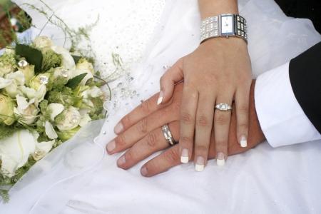 anillos de boda: Amante de las manos de explotaci�n de la pareja con anillos contra el vestido de novia