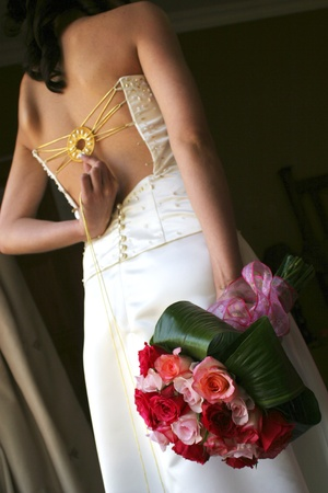 Bride holding white and pink roses and golden circle at back Stock Photo - 8600813