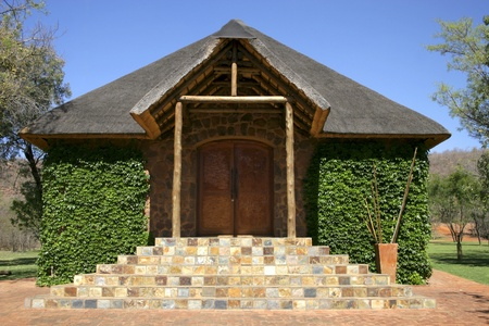 Stone chapel with thatch roof covered in green ivy against blue sky Stock Photo