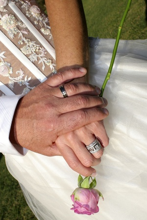 Loving couple holding hands with rings and a single pink rose against wedding dress