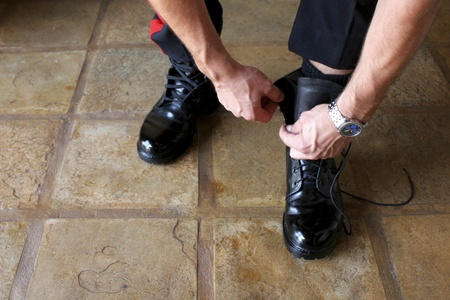 Close up on man in uniform putting on black boots Stock Photo