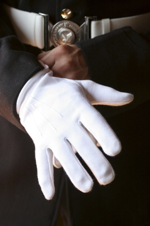 Close up on man in uniform putting on white gloves