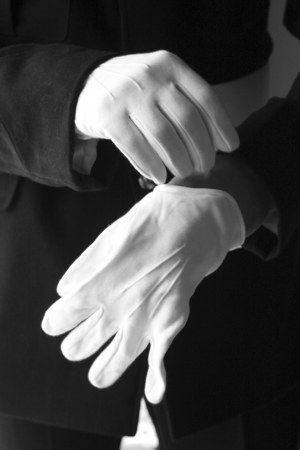 white glove: Close up on man in uniform putting on white gloves