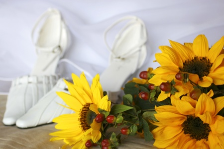 Yellow sunflowers with brides white shoes in background