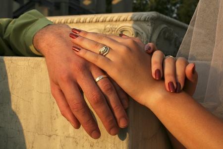 Pareja amorosa con manos contra agrietado pilar mostrando sus anillos de boda Foto de archivo - 8775823