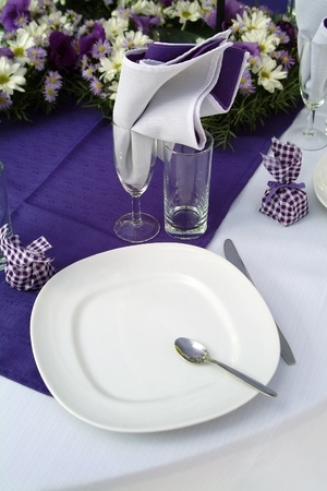 Purple place setting with white cutlary and white and purple daisies Stock Photo