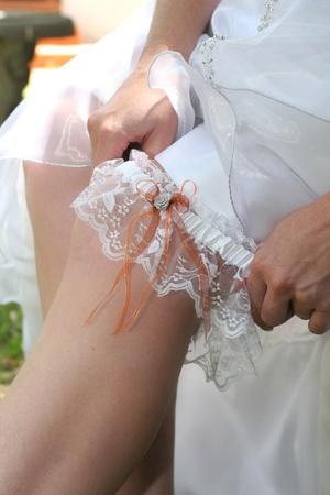 Bride in white wedding dress putting on garter belt Stock Photo