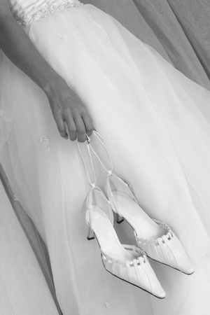 Diagonal close up on bride holding white shoes at her side