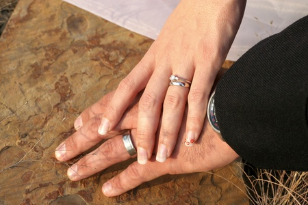 Couple holding hands with wedding rings against sandstne background