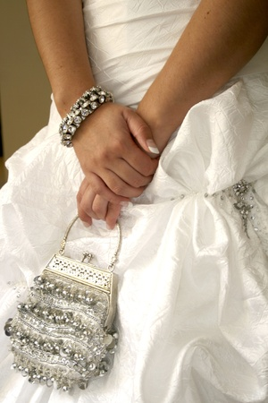 Close up of bride holding silver handbag with both hands Stock Photo
