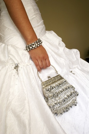 Close up of bride holding handbag at her side